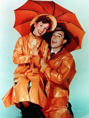 """Debbie Reynolds poses with Gene Kelly in a publicity still from """"Singin' in the Rain."""""""