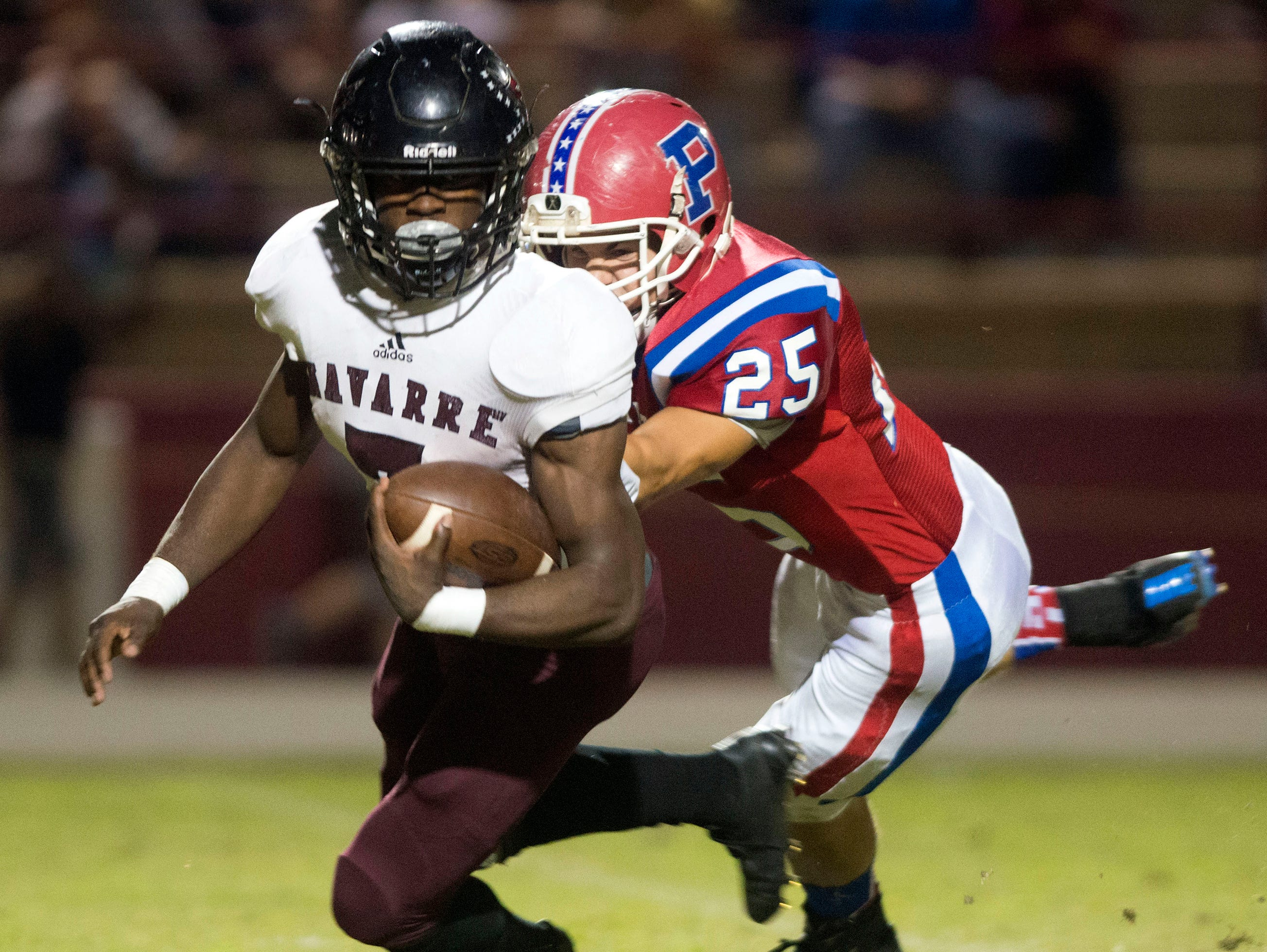 Navarre High School star running back Michael Carter (No. 7) gets wrapped up behind the line of scrimmage by the Pace High School line backer, Gatlin Lowe, (No.25) during the District 2-6A matchup Friday night.