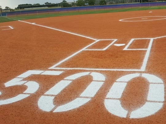 "Lincoln Park Academy Athletic Director Jill Corey presented softball coach Roger Mathews with a commemorative plaque and banner on a softball field chalked with special ""500"" markings in recognition of his 500 career wins."