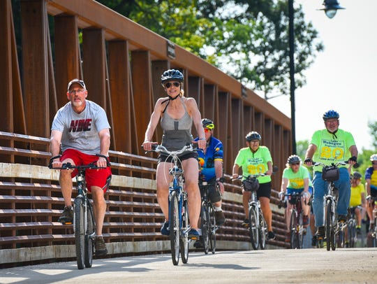 Bike riders cross the new bridge into Waite Park on