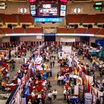Expo attendees walk past booths during the Louisiana Gulf Coast Oil Exposition, or LAGCOE, at the Cajundome Convention Center.