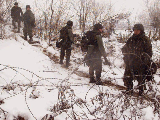 U.S. Army soldiers walk through the snow as they patrol the perimeter of Tuzla airbase on Dec. 19, 1995. They were in Bosnia as part of the NATO Implementation Force to enforce the Bosnia peace agreement.