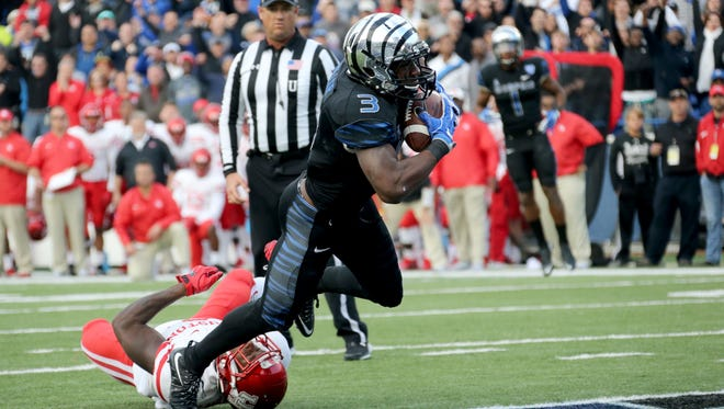 Memphis wide receiver Anthony Miller (3) dives into the end zone after breaking a tackle attempt by Houston's Khalil Wiliams, left, for the game-winning touchdown in the second half of an NCAA college football game Friday, Nov. 25, 2016, in Memphis, Tenn. Memphis defeated Houston 48-44.