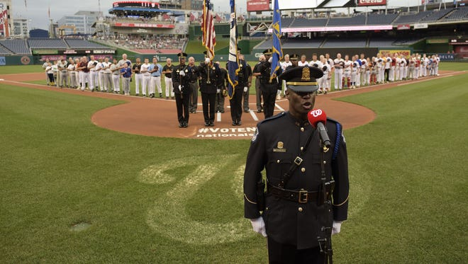 Members of the Democratic and Republican teams listen to the national anthem before the annual congressional baseball game at Nationals Park on June 23, 2016.
