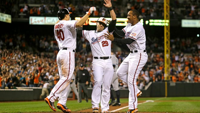 Baltimore Orioles' Steve Pearce, center, celebrates with teammates Nick Hundley, left, and Jonathan Schoop after scoring the winning run on a double by Kelly Johnson in the ninth inning of a baseball game against the New York Yankees, Sunday, Sept. 14, 2014, in Baltimore. Baltimore won 3-2. (AP Photo/Patrick Semansky)