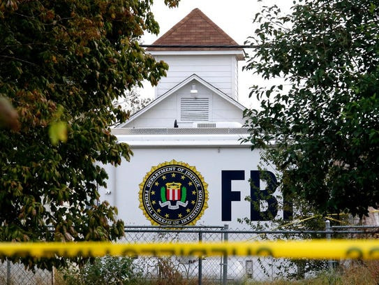 A FBI truck sits in front of the church while investigators