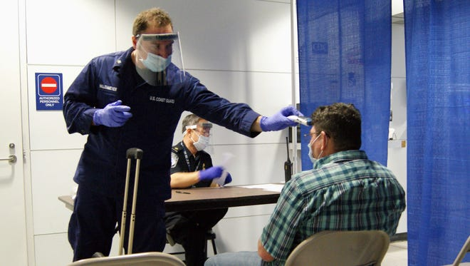 In this photo released by U.S. Customs and Border Protection, U.S. Coast Guard Health Technician Nathan Wallenmeyer, left, and CBP supervisor Sam Ko conduct prescreening measures on a passenger, right, who arrived from Sierra Leone at O'Hare International Airport's Terminal 5 in Chicago.