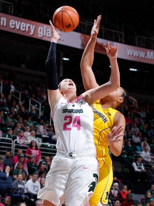 Michigan State's Lexi Gussert puts up a layup against Michigan's JIllian Dunston, Sunday, Feb. 11, 2018, in East Lansing, Mich. MSU won 66-61.