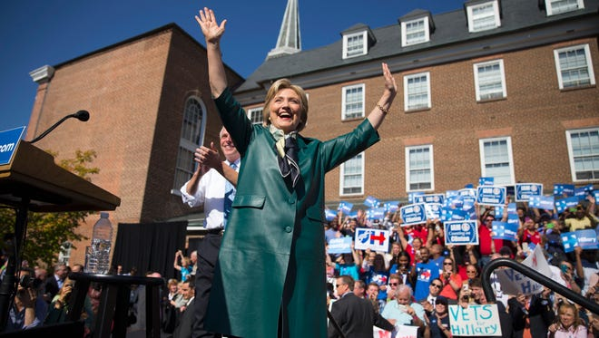 Hillary Clinton, accompanied by Virginia Gov. Terry McAuliffe, smiles and waves as she arrives for a campaign rally in Alexandria, Va., on Oct. 23, 2015.