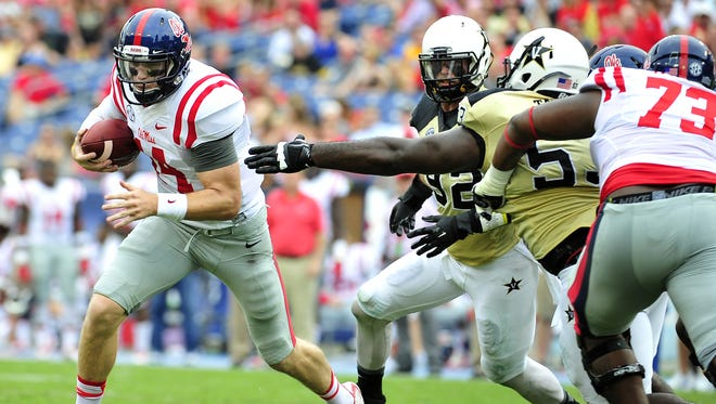 Ole Miss quarterback Bo Wallace, left, gets away from a tackle by Vanderbilt's Vince Taylor during the first quarter at LP Field in Nashville, Tenn., Saturday, Sept. 6, 2014.