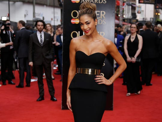 Singer Nicole Scherzinger poses for photographers upon arrival at the Olivier Awards at the Royal Opera House in central London, Sunday, April 12, 2015.