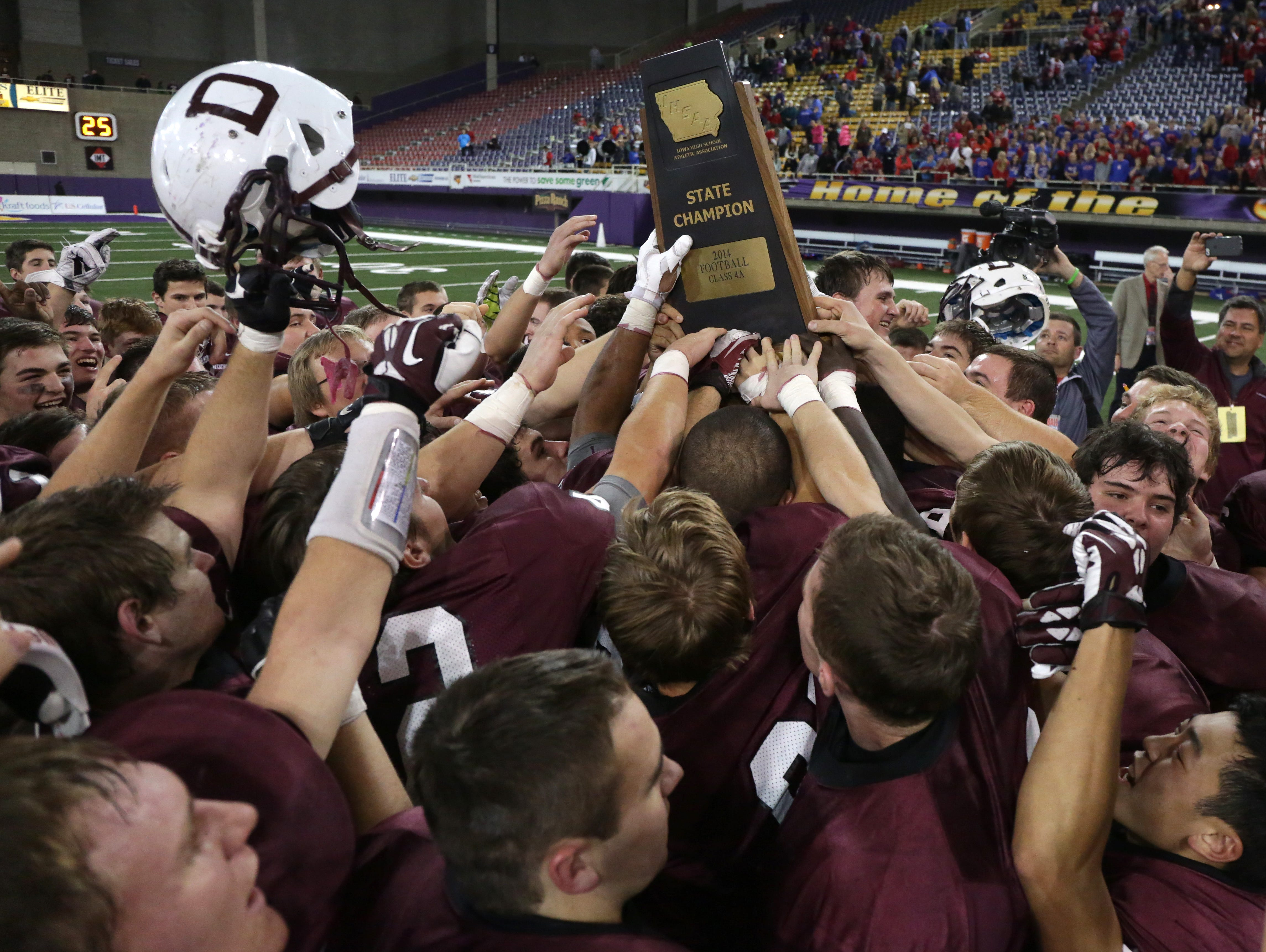 Members of the Dowling Catholic football team celebrate with their trophy after a win over Cedar Rapids Washington in the Iowa Class 4A state football championship game on Friday, Nov. 21, 2014, at the UNI-Dome in Cedar Falls, Iowa.