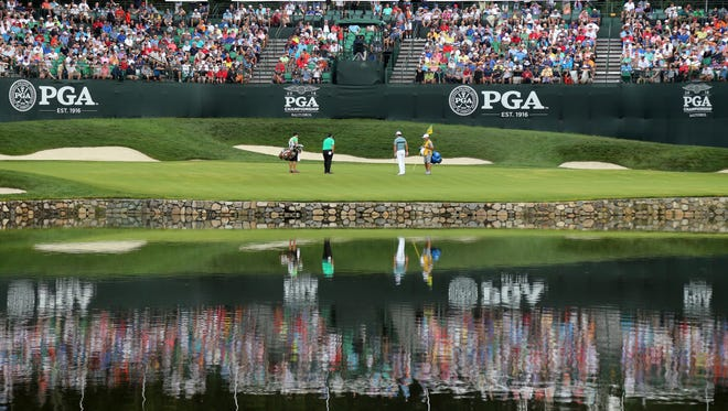 Patrick Reed, second from left, and Brooks Koepka, second from right, play the fourth hole during the final round of the PGA Championship golf tournament at Baltusrol Golf Club in Springfield, N.J., Sunday, July 31, 2016. (AP Photo/Seth Wenig)