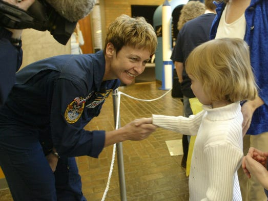 NASA astronaut Peggy Whitson, left, shakes hands with