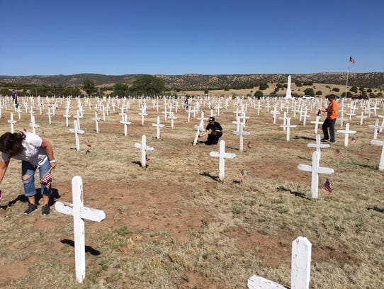 Volunteers turned out to help place flags at each grave