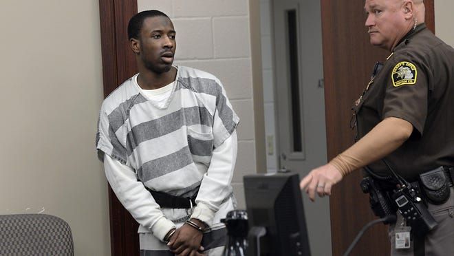 Timothy Minor III enters court in Lansing on Wednesday for sentencing on two weapons charges in connection with the 2013 shooting near Sexton High School.