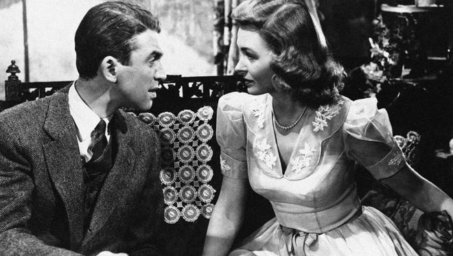 "Jimmy Stewart explains things to Donna Reed in 'It's s a Wonderful Life""' in 1946. The holiday classic is celebrating its 70th anniversary."