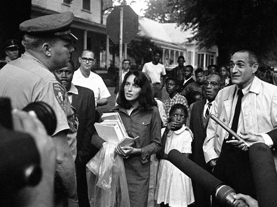 Joan Baez with a small child as the folk singer walked with black children to school in Grenada, Miss., Sept. 19, 1966 during integration. She marched there with Martin Luther King, Jr.