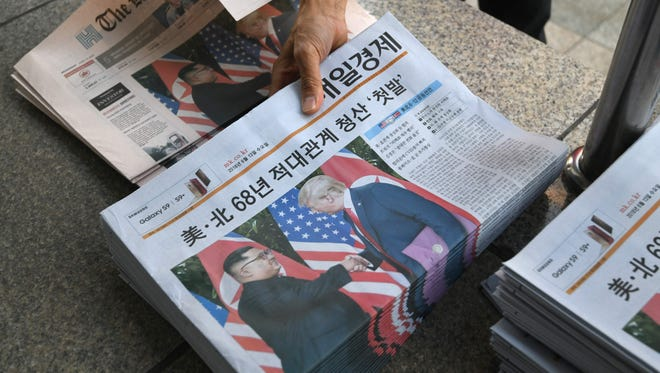 A South Korean newspaper deliveryman collects newspapers in Seoul reporting the summit between President Trump and North Korean leader Kim Jong Un on June 12, 2018.