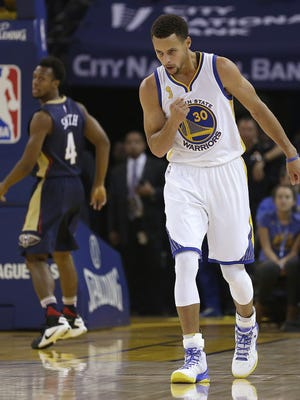 Golden State Warriors' Stephen Curry celebrates a basket against the New Orleans Pelicans during the first half of an NBA basketball game Tuesday, Oct. 27, 2015, in Oakland, Calif.