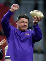 LSU head coach Ed Orgeron holds up the trophy after