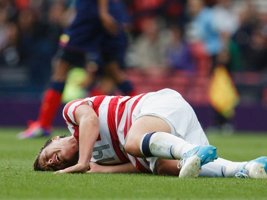 Abby Wambach lays on the field after suffering an injury at the hands of Colombia's Lady Andrade during the London 2012 Summer Olympics.