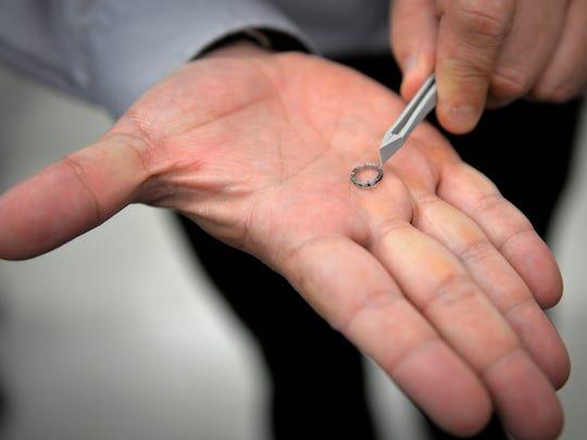 Novak holds a tiny TMX leak-proof, crushable seal made