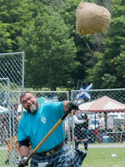 Brent Miller tosses the sheaf, a 20-pound sack of hay,