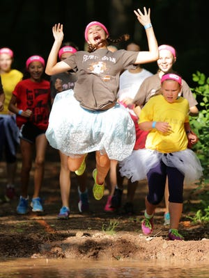 """Jasmin Bryan-Moreira of Neenah takes a running leap into the """"Slop Bath"""" obstacle during the first annual Filthy Fun Kids Run at O'Hauser Park in Neenah, Wis., Saturday, July 11, 2015. The event challenge was sponsored by the City of Neenah and the Town of Menasha Parks and Recreation Departments."""