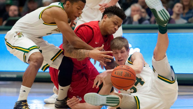 The University of Vermont's Trae Bell-Haynes, left, and Kurt Steidl, right, go after a loose ball against Stony Brook's Rayshaun McGrew in Burlington on Saturday, January 30, 2016.