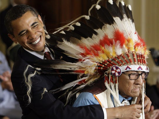 President Barack Obama reaches around the head dress