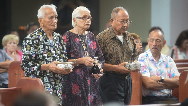 War surivors deliver the offertory during a Mass in honor of 