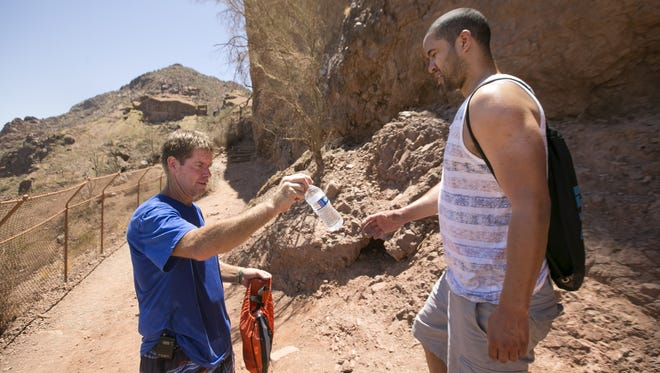 Scott Cullymore of Mesa hands a bottle of water to Zach Smith of New York City while hiking the Echo Canyon Trail on Camelback Mountain in Phoenix on June 28, 2016. Cullymore hikes to the top of Camelback Mountain every day handing out bottles of water to those who need them.