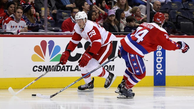 Anthony Mantha (39) of the Detroit Red Wings moves the puck past John Carlson of the Washington Capitals on Nov. 18, 2016, in Washington, DC.