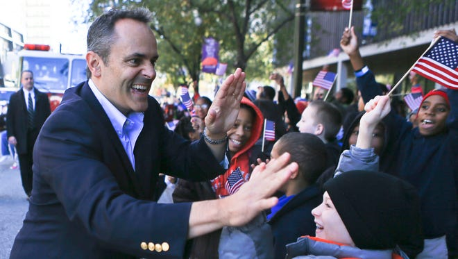 Kentucky Governor-elect Matt Bevin gave high fives to elementary students as he walked the Veterans Day parade on Main Street Wednesday in Louisville.