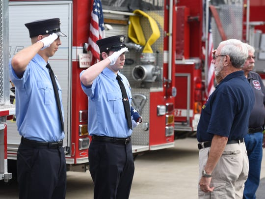 Hughsonville firefighters, from left, Matt Messina and Alexander Lorenzini accept a flag from Arlington Fire District First Assistant Chief John Richardson on Wednesday. Arlington Fire District was ordered to remove flags from their apparatus, Hughsonville offered to take one of the flags and fly it from one of their apparatus.