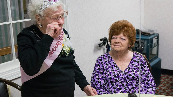 Jean Proch, at right, watches her mother, Marion Langley, react to attention received on her 100th birthday.