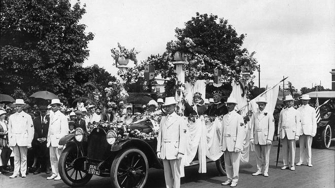 The Cherrians are seen walking along side the car carrying the king and queen of the Cherry Festival in 1916. P 0063.001.0073.002.22 / Willamette Heritage Center