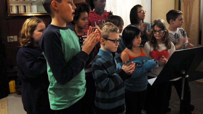 Members of the Boys & Girls Club of Door County keep the beat by clapping to the rhythm of the club's new song inside Studio 330 in Sturgeon on Nov. 11.