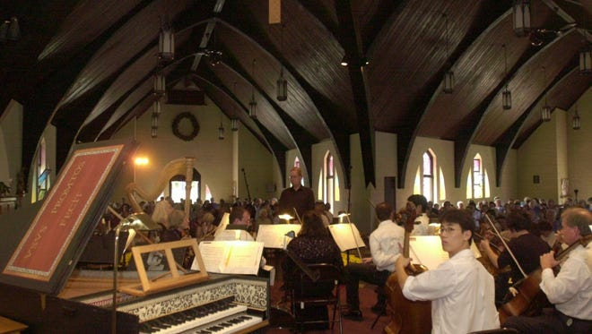 Musicians tune up as audience members settle in at St. Denis Catholic Church in Lexington for one of the concerts presented during the annual Lexington Bach Festival.