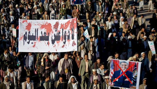 """Houthi Shiite Yemenis holding posters of President Obama, and a banner, left, with Arabic that reads,""""no more ISIL after today,"""" march during a rally to show support for their comrades in Sanaa, Yemen, on Jan. 28, 2015."""
