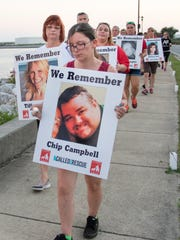 Brittany Flores carries the photo of her second cousin Chip Campbell during the Missing Person's Community Awareness Walk organized by the KlassKids Foundation in Pensacola on Wednesday, September 28, 2016.  Campbell has been missing for 6 months.