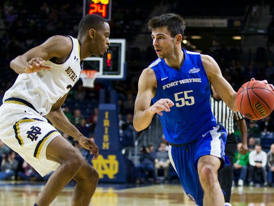 IPFW's John Konchar (55) drives next to Notre Dame's