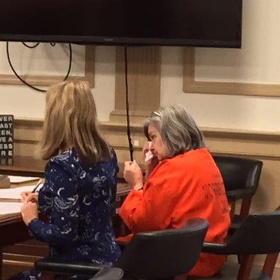Debra Boucher wipes away tears after pleading guilty