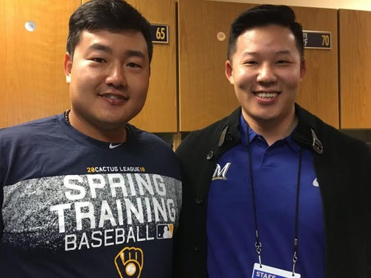 Brewers prospect Ji-Man Choi (left) poses in the clubhouse with translator Daniel Cho.