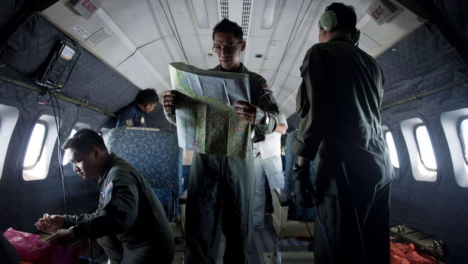 A Royal Malaysian Air Force Navigator captain, Izam Fareq Hassan, center, looks at a map onboard a Malaysian Air Force CN235 aircraft during a search and rescue operation to find the missing Malaysia Airlines flight MH370 on March 14, 2014.