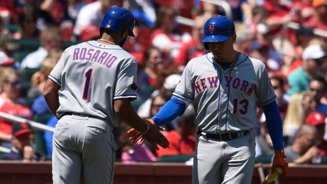 New York Mets shortstop Amed Rosario (1) is congratulated by shortstop Asdrubal Cabrera (13) after scoring a run against the St. Louis Cardinals during the seventh inning at Busch Stadium.