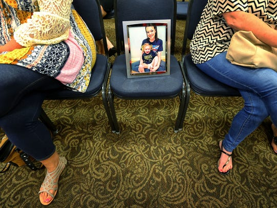 Debra Ward (left) sits with a portrait of her daughter Dallas Roberson and granddaughter Madelyn Martin during an opioid town hall meeting at the Landers Center in Southaven last year. Roberson, a heroin addict, died of an infection caused by a dirty needle.
