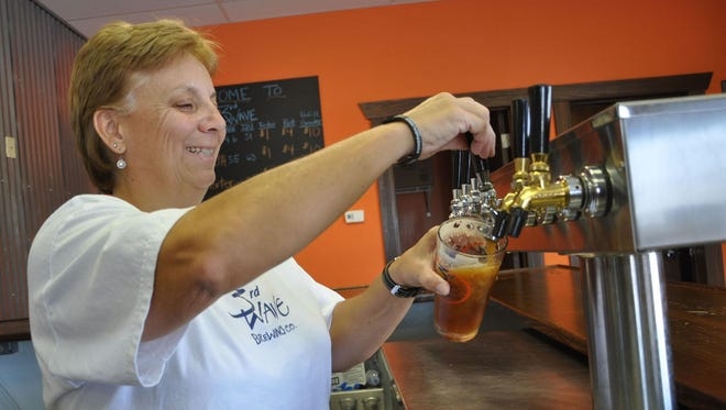 Co-owner and brewery manager Lori Clough pours a beer at 3rd Wave Brewing Co. in Delmar.