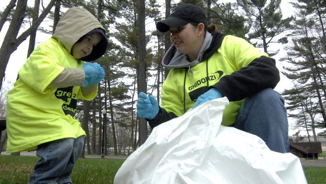 Volunteers Season Schmitz, right, and her son, Isaac, both of Ringle, pick up trash in Marathon Park during the 2011 Ghidorzi Green and Clean.
